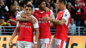 Arsenal's Chilean striker Alexis Sanchez (L) celebrates after scoring with Arsenal's Egyptian midfielder Mohamed Elneny (C) and Arsenal's Swiss midfielder Granit Xhaka during the English Premier League football match between Hull City and Arsenal at the KCOM Stadium in Kingston upon Hull, north east England on September 17, 2016. / AFP / Andy Buchanan / RESTRICTED TO EDITORIAL USE. No use with unauthorized audio, video, data, fixture lists, club/league logos or 'live' services. Online in-match use limited to 75 images, no video emulation. No use in betting, games or single club/league/player publications.  /         (Photo credit should read ANDY BUCHANAN/AFP/Getty Images)