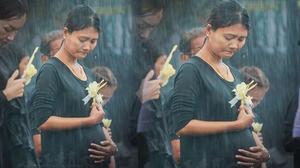 เจอแล้ว หญิงท้องต่อแถวถวายดอกไม้จันทน์ ท่ามกลางสายฝน