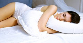 Pretty woman wearing white outfit sleeping on bed