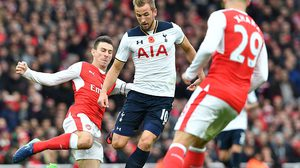 Arsenal's French defender Laurent Koscielny (L) tackles Tottenham Hotspur's English striker Harry Kane (C) during the English Premier League football match between Arsenal and Tottenham Hotspur at the Emirates Stadium in London on November 6, 2016.  Koscielny received a yellow card for the challenge. / AFP / BEN STANSALL / RESTRICTED TO EDITORIAL USE. No use with unauthorized audio, video, data, fixture lists, club/league logos or 'live' services. Online in-match use limited to 75 images, no video emulation. No use in betting, games or single club/league/player publications.  /         (Photo credit should read BEN STANSALL/AFP/Getty Images)